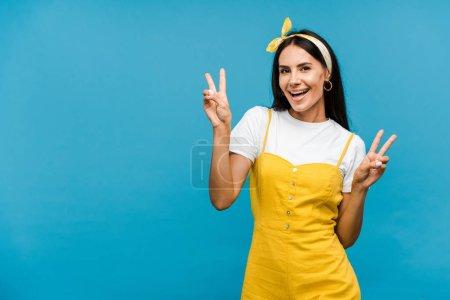 Photo pour Femme heureuse montrant des signes de paix isolé sur bleu - image libre de droit