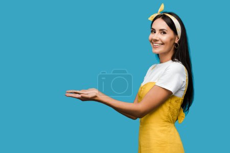Photo for Cheerful young woman in headband gesturing isolated on blue - Royalty Free Image