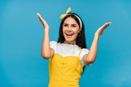 happy young woman in headband gesturing isolated on blue