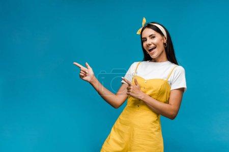 Photo pour Heureuse jeune femme dans bandeau pointant avec les doigts isolés sur bleu - image libre de droit