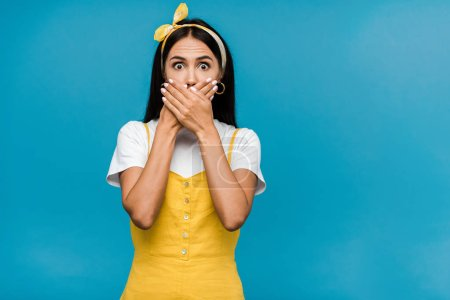 Photo for Scared woman in headband covering mouth isolated on blue - Royalty Free Image