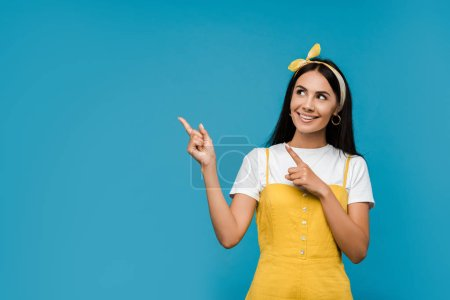 happy woman pointing with fingers isolated on blue