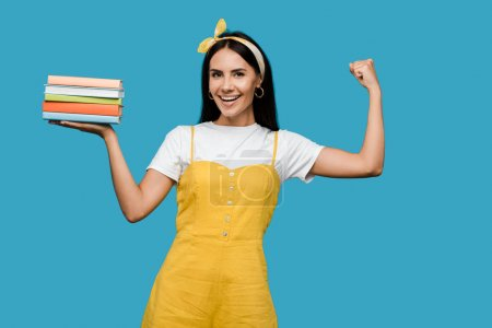 Photo for Happy woman in headband holding books and gesturing isolated on blue - Royalty Free Image