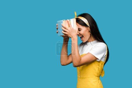 Photo pour Femme émotive criant tout en retenant des livres isolés sur le bleu - image libre de droit