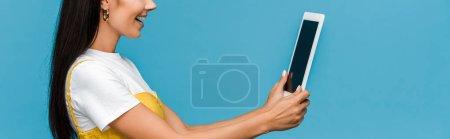 Photo pour Tir panoramique de jeune femme utilisant la tablette numérique d'isolement sur le bleu - image libre de droit