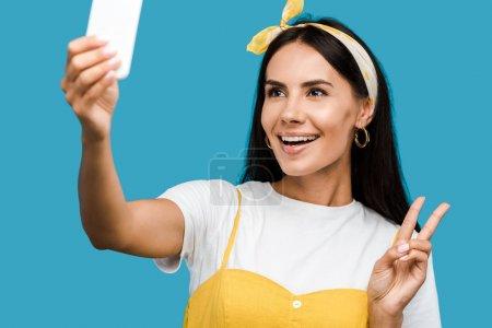 Photo pour Foyer sélectif de femme heureuse prenant selfie sur smartphone tout en montrant signe de paix isolé sur bleu - image libre de droit