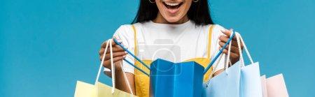 Photo pour Plan panoramique de jeune femme heureuse tenant des sacs à provisions colorés isolés sur bleu - image libre de droit