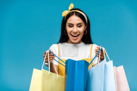 Photo for Happy young woman looking at shopping bags isolated on blue - Royalty Free Image