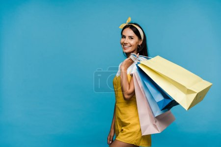 Photo for Happy young woman standing with colorful shopping bags isolated on blue - Royalty Free Image