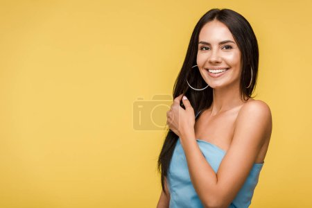 Photo for Happy young woman smiling while looking at camera isolated on orange - Royalty Free Image
