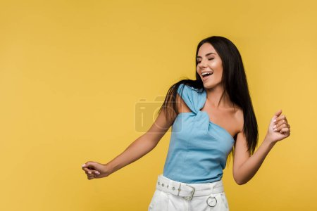 Photo for Happy young woman with closed eyes gesturing isolated on orange - Royalty Free Image