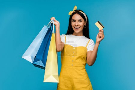 Photo for Happy girl holding credit card and shopping bags isolated on blue - Royalty Free Image