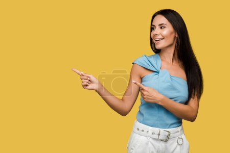 cheerful young woman pointing with fingers isolated on orange