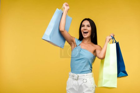 Photo for Excited woman smiling while holding shopping bags on orange - Royalty Free Image