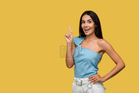 Photo for Happy woman with hand on hip pointing with finger isolated on orange - Royalty Free Image