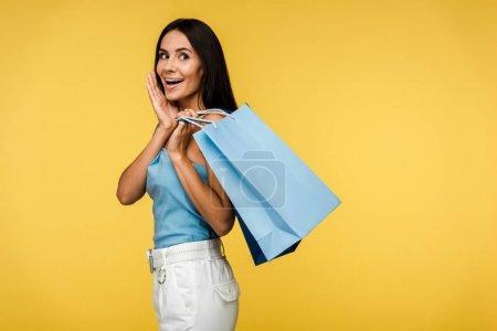 Photo pour Excité femme tenant sacs à provisions isolé sur orange - image libre de droit