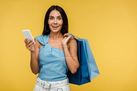 Photo for Excited young woman looking at camera and holding smartphone with shopping bags isolated on orange - Royalty Free Image