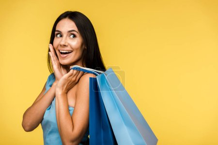 Photo for Excited young woman holding shopping bags isolated on orange - Royalty Free Image