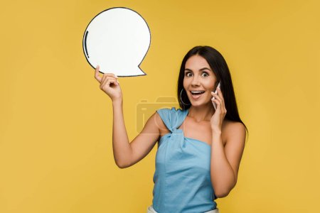 Photo for Happy girl holding blank speech bubble while talking on smartphone isolated on orange - Royalty Free Image