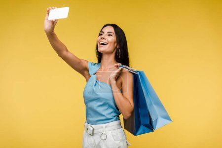 Photo for Happy woman holding shopping bags and taking selfie on smartphone on orange - Royalty Free Image
