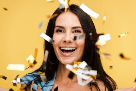 Photo for Selective focus of happy woman near sparkling confetti on orange - Royalty Free Image