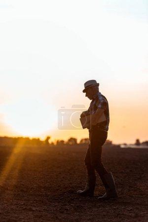 Photo pour Vue latérale de fermier dans la boîte en bois de chapeau de paille tout en marchant pendant le coucher du soleil - image libre de droit