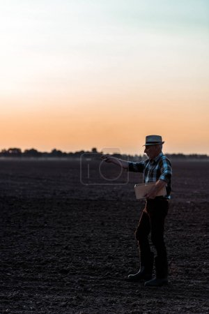 Photo for Profile of self-employed man in straw hat standing and sowing seeds - Royalty Free Image