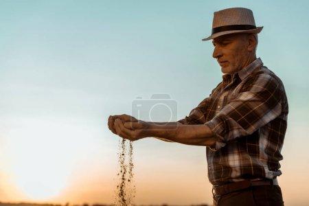 Photo pour Fermier indépendant aîné dans le chapeau de paille semer des graines le soir - image libre de droit