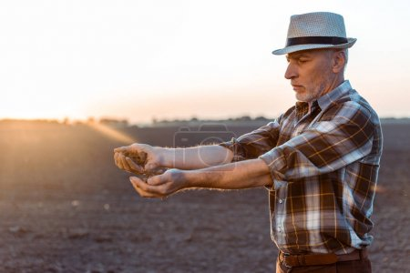 Photo pour Fermier indépendant dans le chapeau de paille semer des graines le soir - image libre de droit