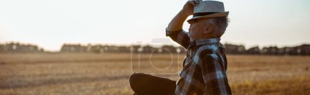 Photo for Panoramic shot of bearded farmer touching straw hat - Royalty Free Image