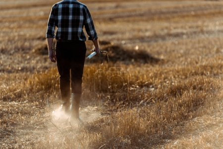 Photo for Cropped view of senior man holding rake while walking wheat field - Royalty Free Image