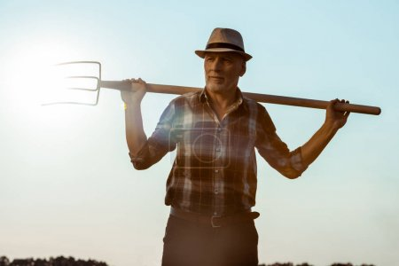 Photo for Happy senior man holding rake against blue sky - Royalty Free Image
