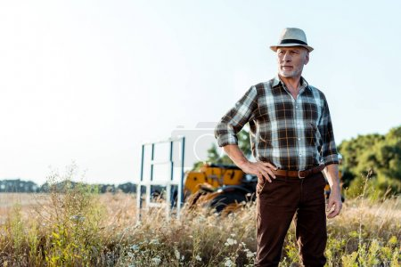 Photo for Senior man in straw hat standing with hand on hip near tractor - Royalty Free Image