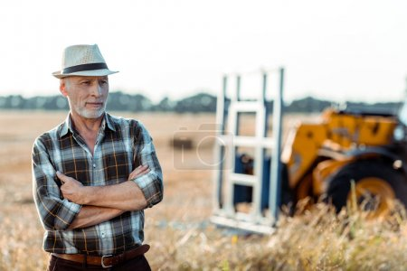 self-employed farmer in straw hat standing with crossed arms near tractor