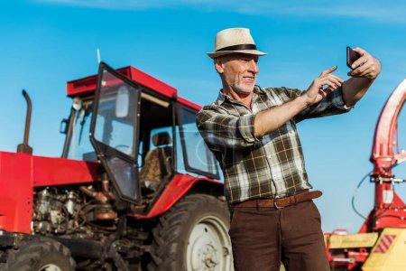 Foto de Enfoque selectivo de agricultor autónomo feliz tomando selfie cerca de tractor - Imagen libre de derechos