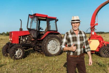 Foto de Feliz agricultor autónomo en sombrero de paja mostrando pulgar hacia arriba cerca de tractor - Imagen libre de derechos