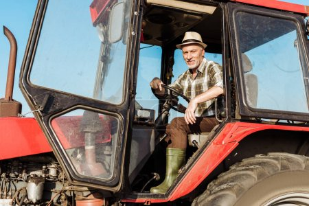 Photo for Happy senior self-employed farmer in straw hat driving tractor - Royalty Free Image