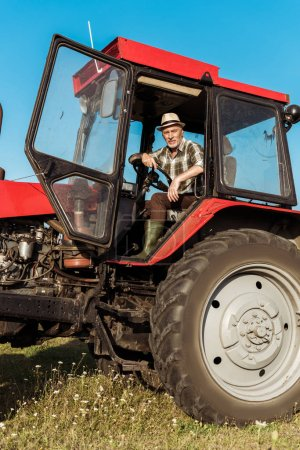 Photo for Senior self-employed farmer in straw hat driving tractor - Royalty Free Image