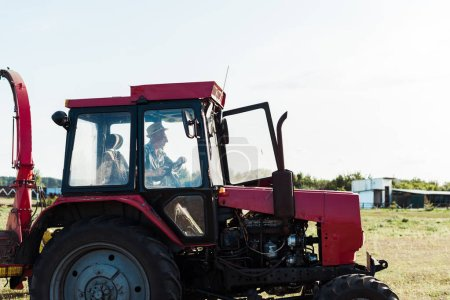 Photo for Bearded senior farmer in straw hat driving tractor - Royalty Free Image