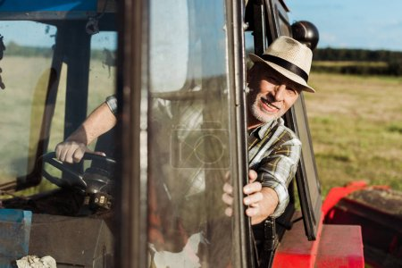 Photo for Selective focus of cheerful senior farmer driving tractor - Royalty Free Image