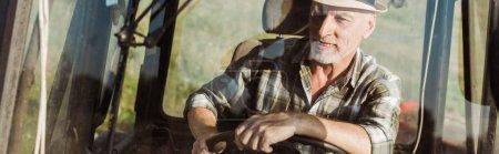 Foto de Disparo panorámico de agricultor autónomo en el sombrero de paja de conducción tractor - Imagen libre de derechos