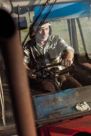 Foto de Enfoque selectivo de apuesto agricultor autónomo sonriendo mientras conduce tractor - Imagen libre de derechos
