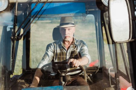 Photo for Selective focus of senior self-employed man driving tractor - Royalty Free Image