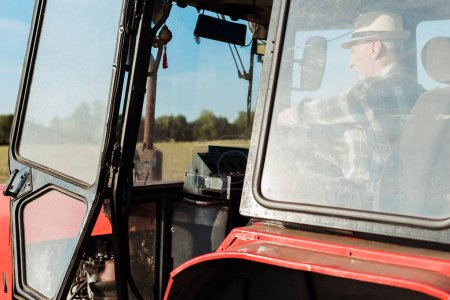 Photo for Self-employed man in straw hat driving tractor - Royalty Free Image