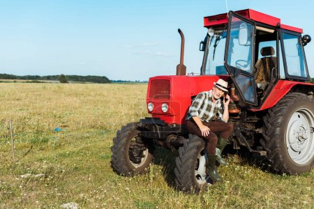 Photo for Bearded agronomist talking on smartphone near tractor - Royalty Free Image