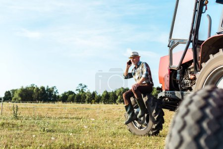 Photo for Selective focus of agronomist talking on smartphone near tractor - Royalty Free Image