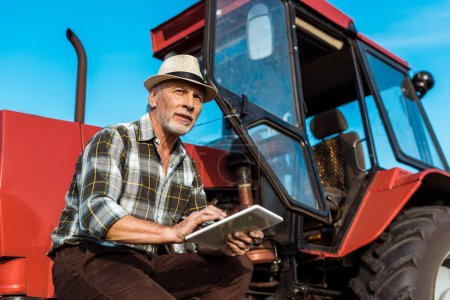 Photo for Senior farmer in straw hat using digital tablet near red tractor - Royalty Free Image