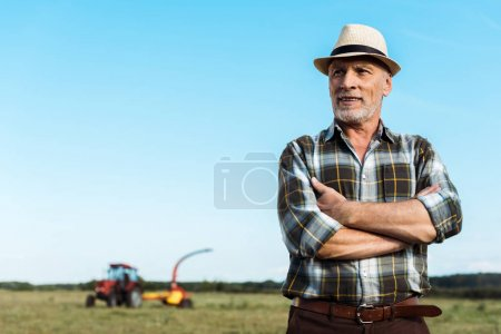 Photo for Bearded senior farmer standing with crossed arms in field - Royalty Free Image