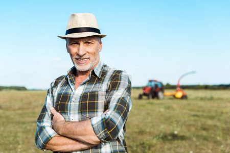 Photo for Happy senior farmer standing with crossed arms in field - Royalty Free Image