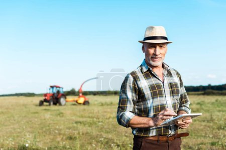 Photo for Cheerful farmer in straw hat using digital tablet in field - Royalty Free Image